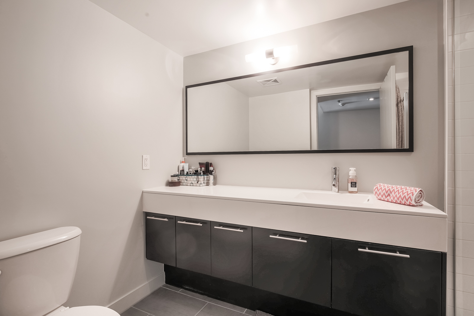 Photo showing 1 of the condo's 2 large bathrooms. This one has a wide, gorgeous mirror and clean lines