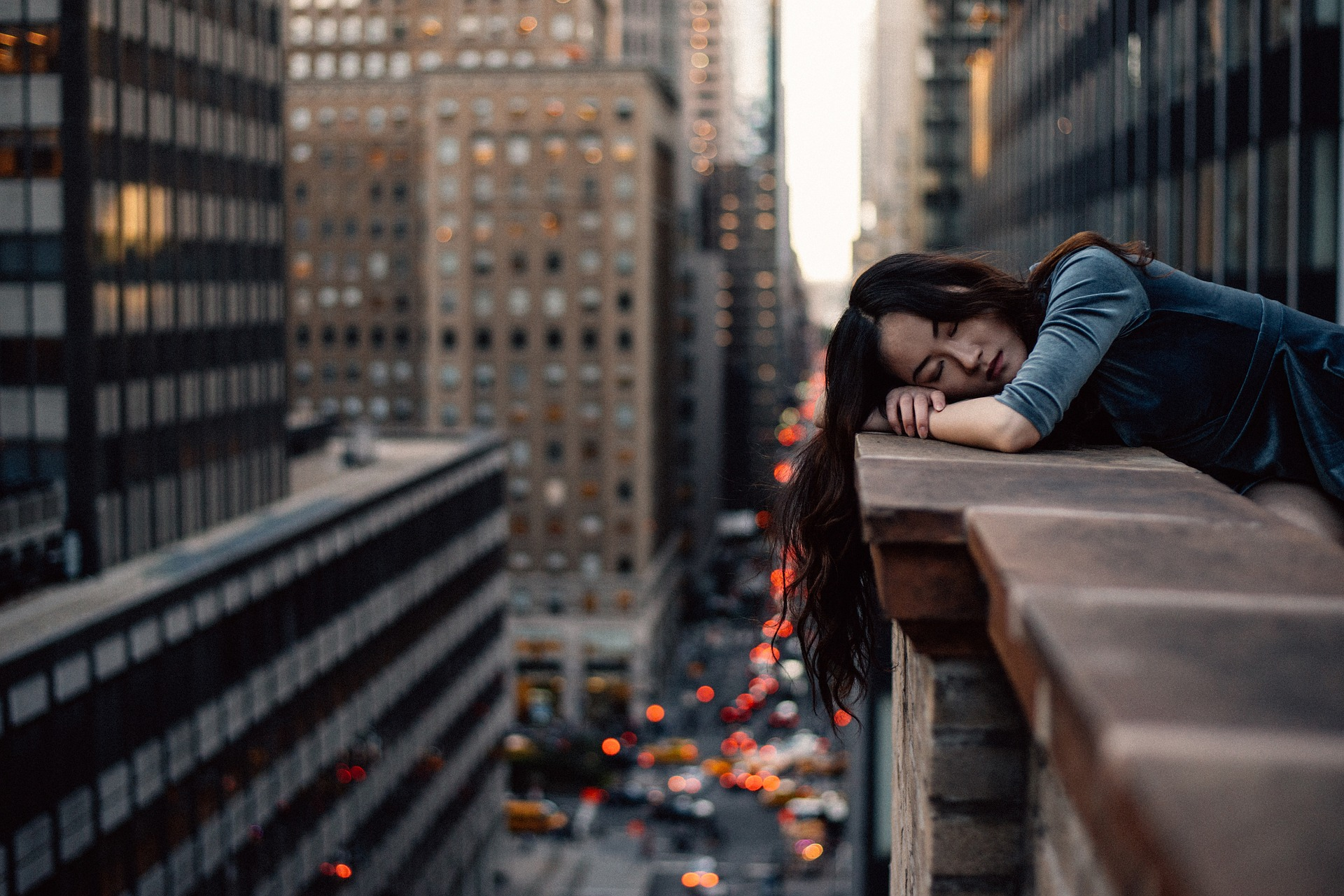 Image of young woman resting her head on balcony overlooking busy streets