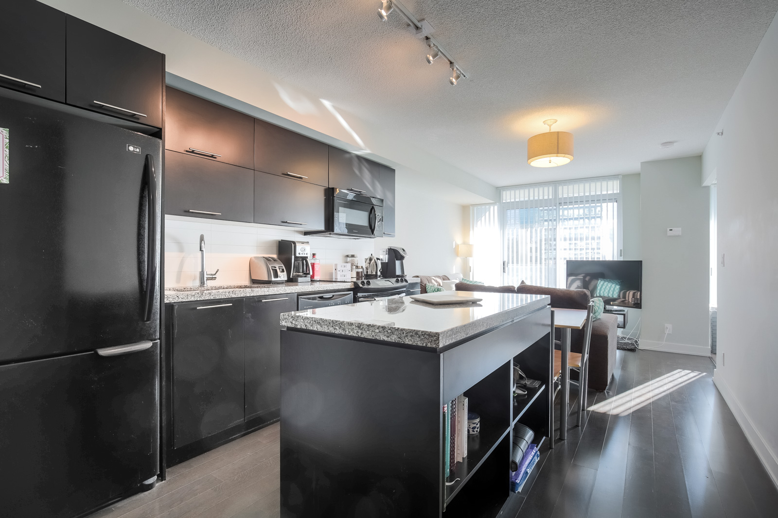 View of condo interior showing modern, open-concept design, hardwood floors & stainless steel appliances