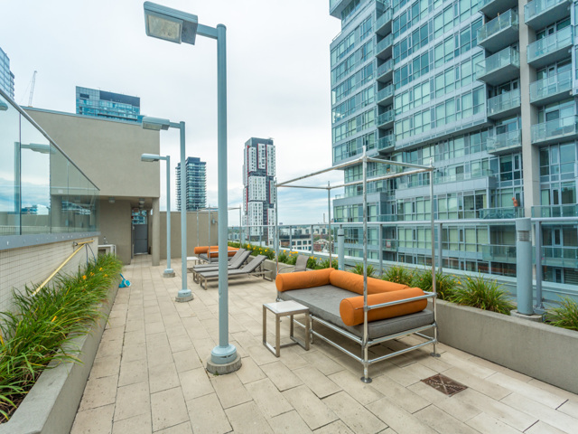 View of rooftop lounge with lamps and buildings