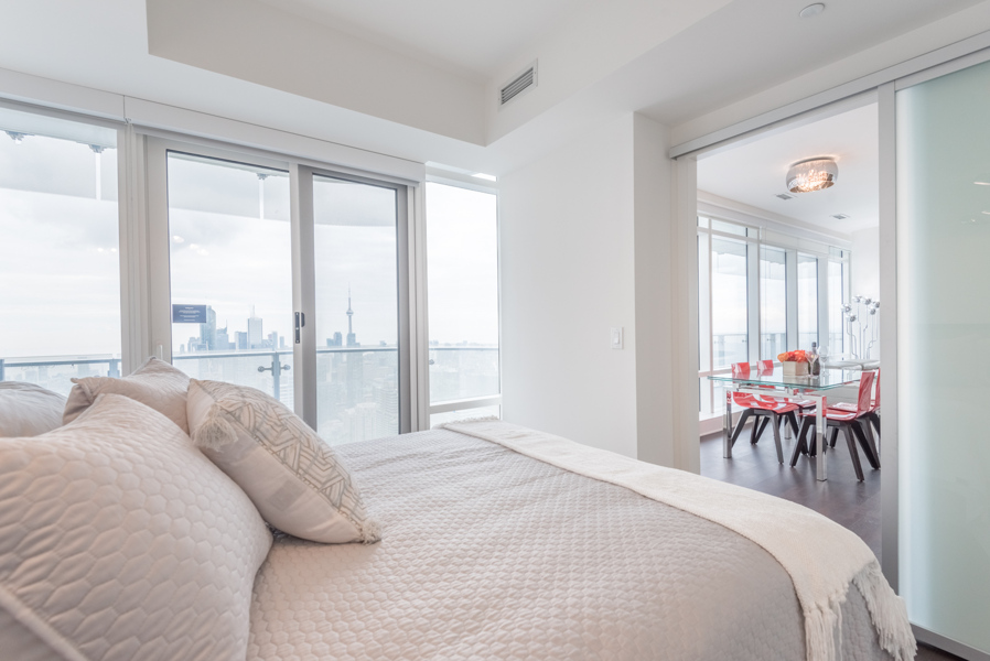 Image of bedroom with glimpse of kitchen and Toronto skyline