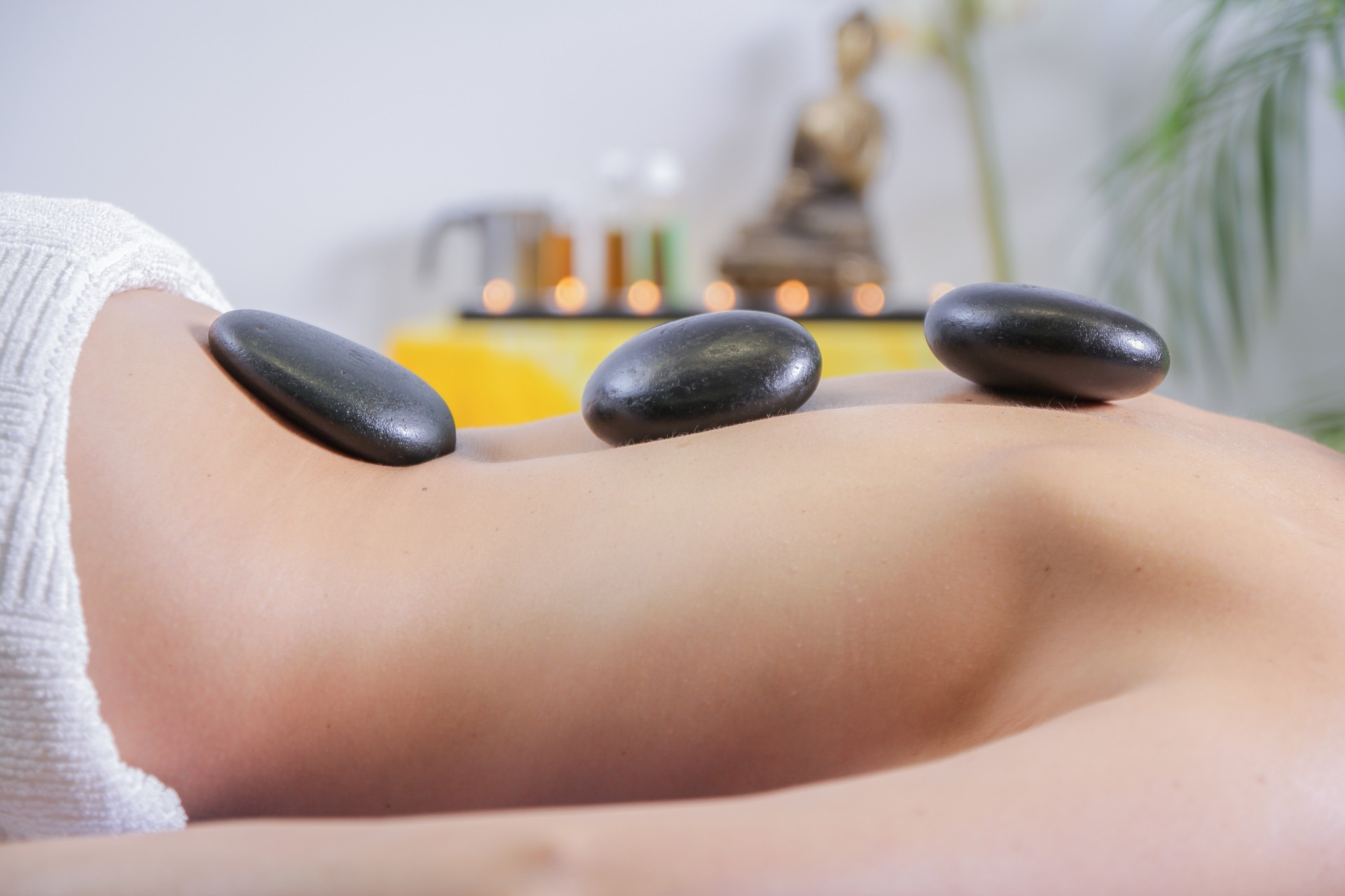 Image of hot stone therapy showing woman's back with 3 dark, circular stones