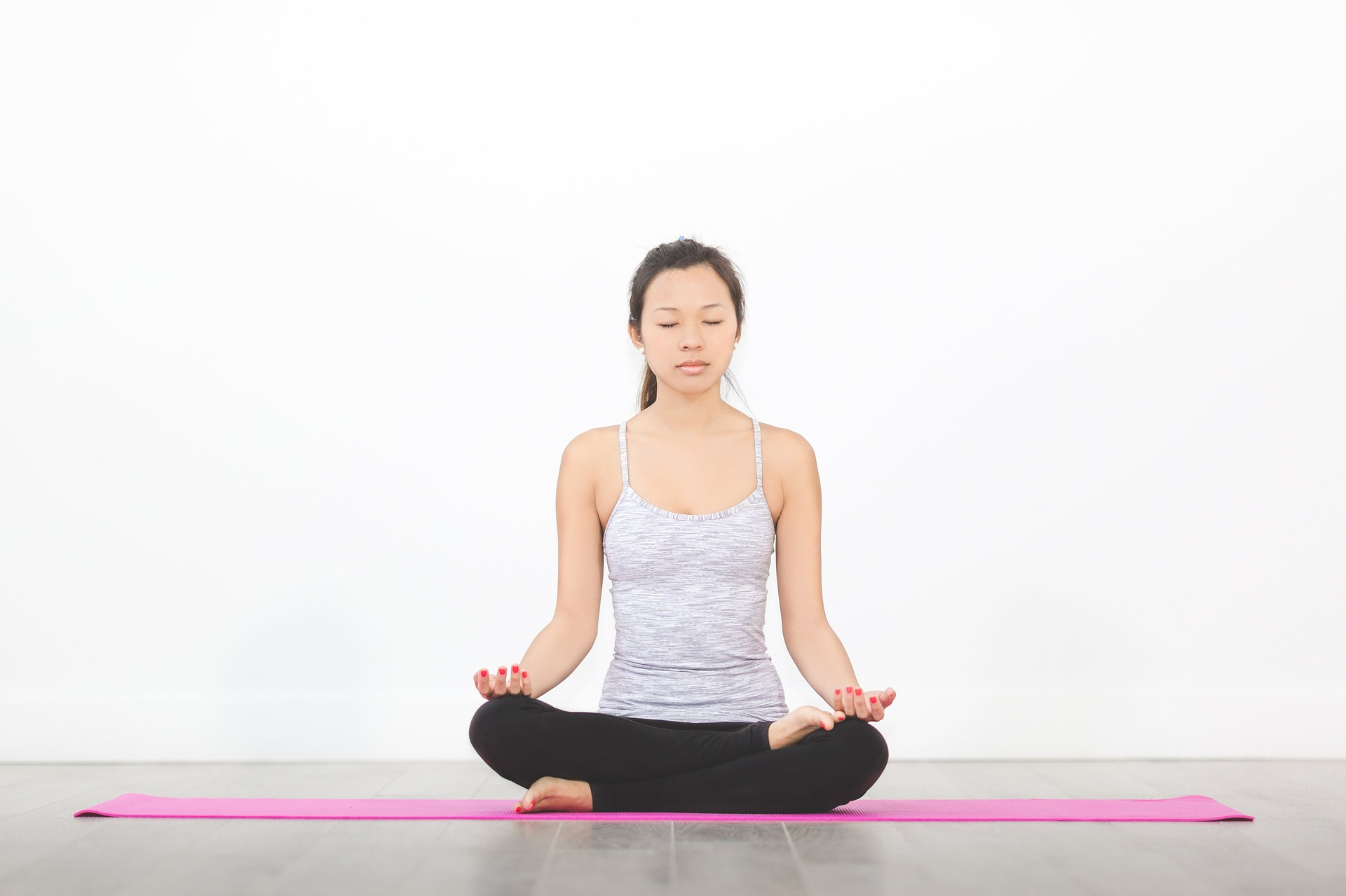 Image depicting woman practicing Yoga and meditation on pink Yoga mat