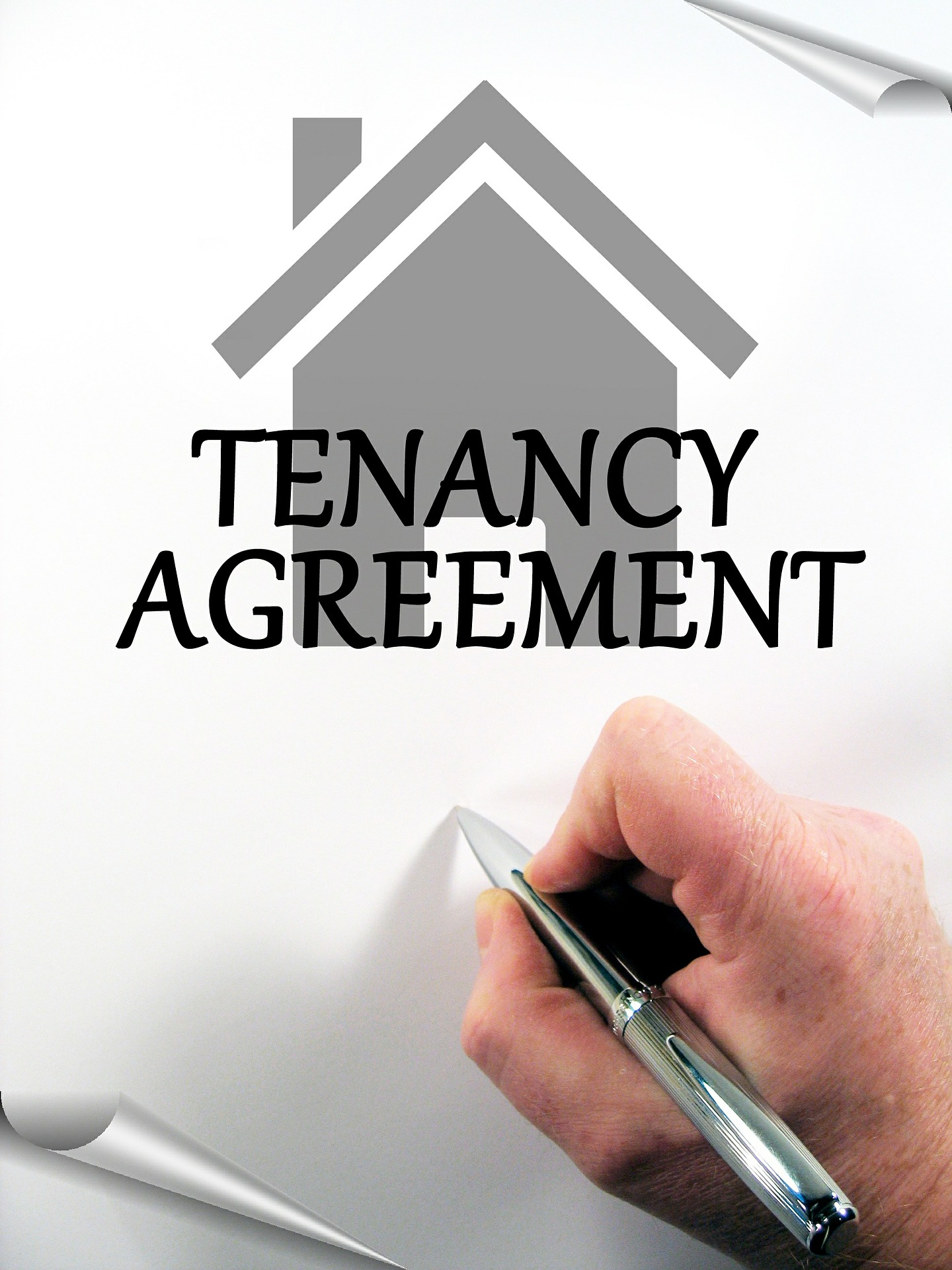 """Photo of hand holding pen over a piece of paper saying """"Tenancy Agreement."""" There's a house; best real estate agents in Toronto."""