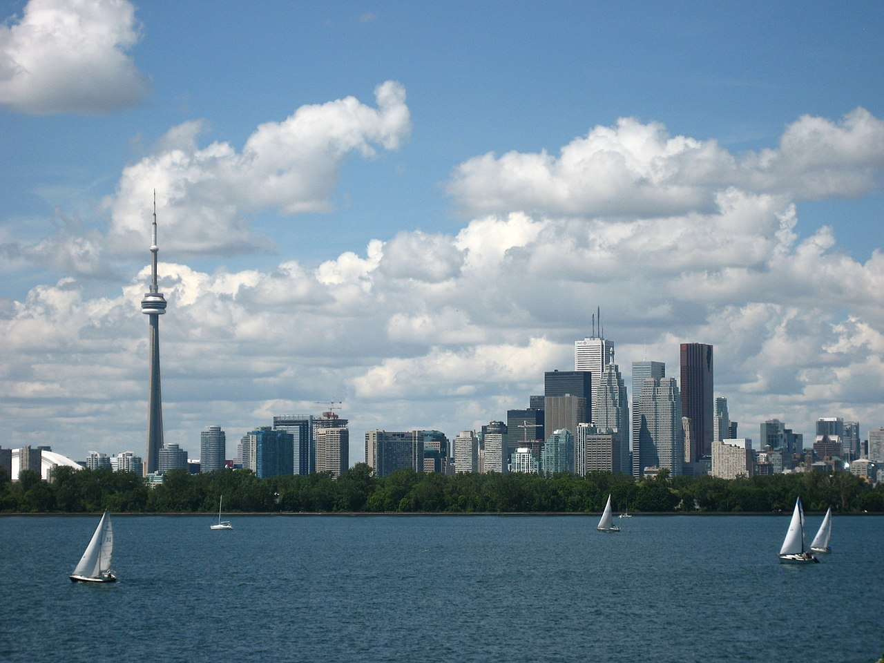 Photo shows Toronto Waterfront from Lake Ontario. In addition to the CN Tower, we can also see boats and so many buildings. Therefore, in conclusion it seems like, maybe, probably, which almost, most of all, most noteworthy, especially relevant to it.