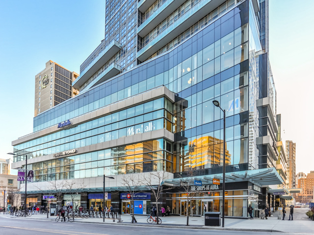 Photo of 384 Yonge Street from distance. View shows so many windows, almost blue in colour, in addition to people and also bicycles.