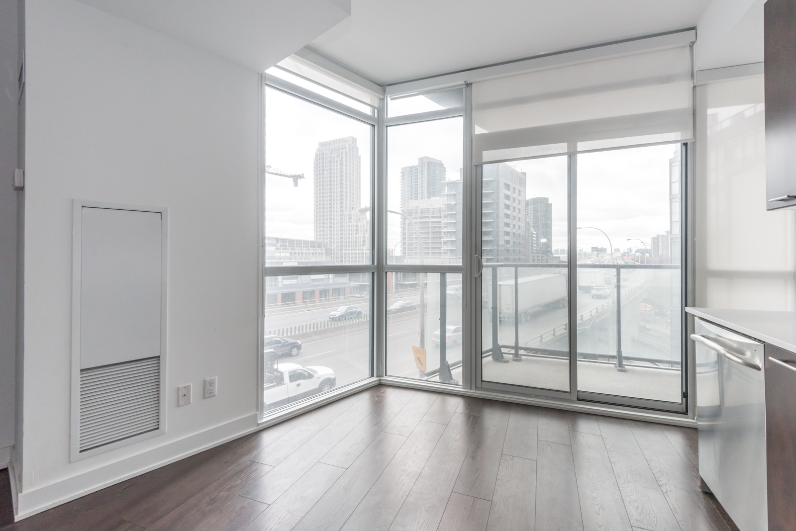 This photo shows the condo's large windows and so much of the city beyond. There's also blinds for privacy. Furthermore, we can see the balcony and yet another gorgeous view of Toronto.