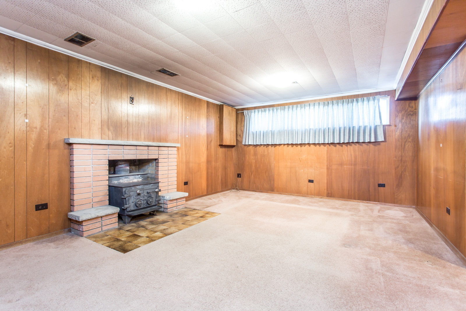 Rec room with carpet and furnace. Almost all of it is covered in carpet, while the walls have wooden panels.