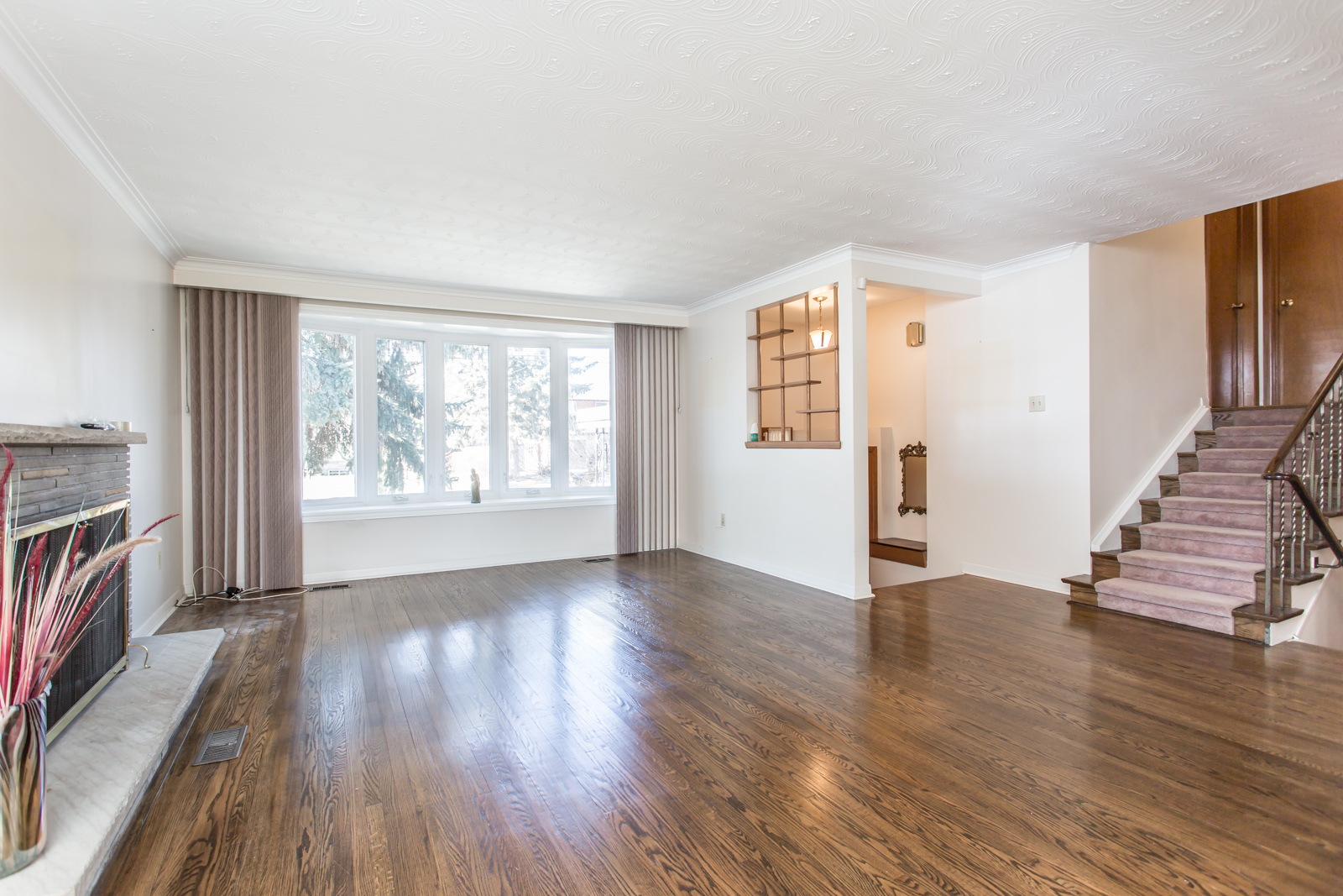 Image shows living room, hardwood floors, and rather wide windows.