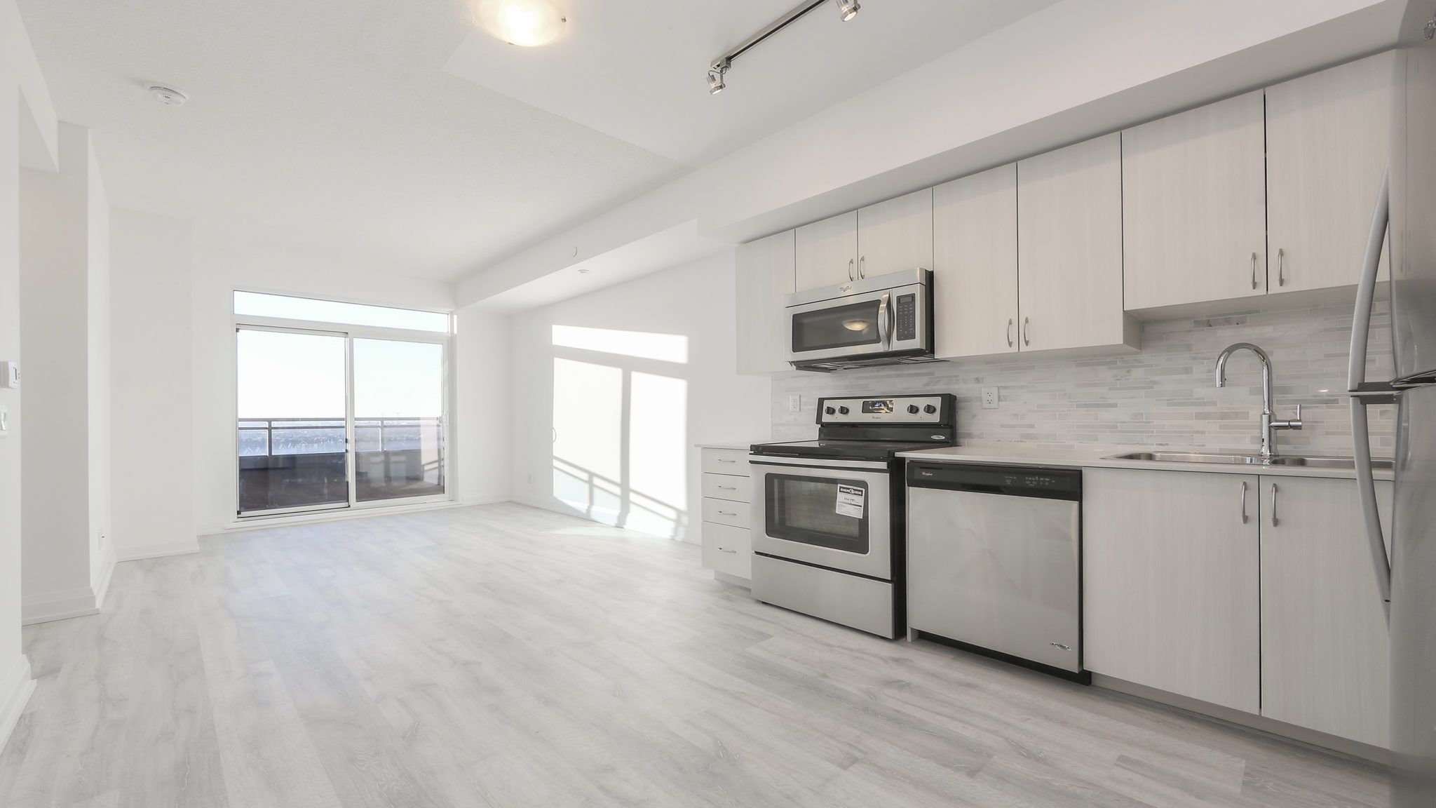 Another image showing the condo's open-concept style and lovely design. Here we see the kitchen and dining room.