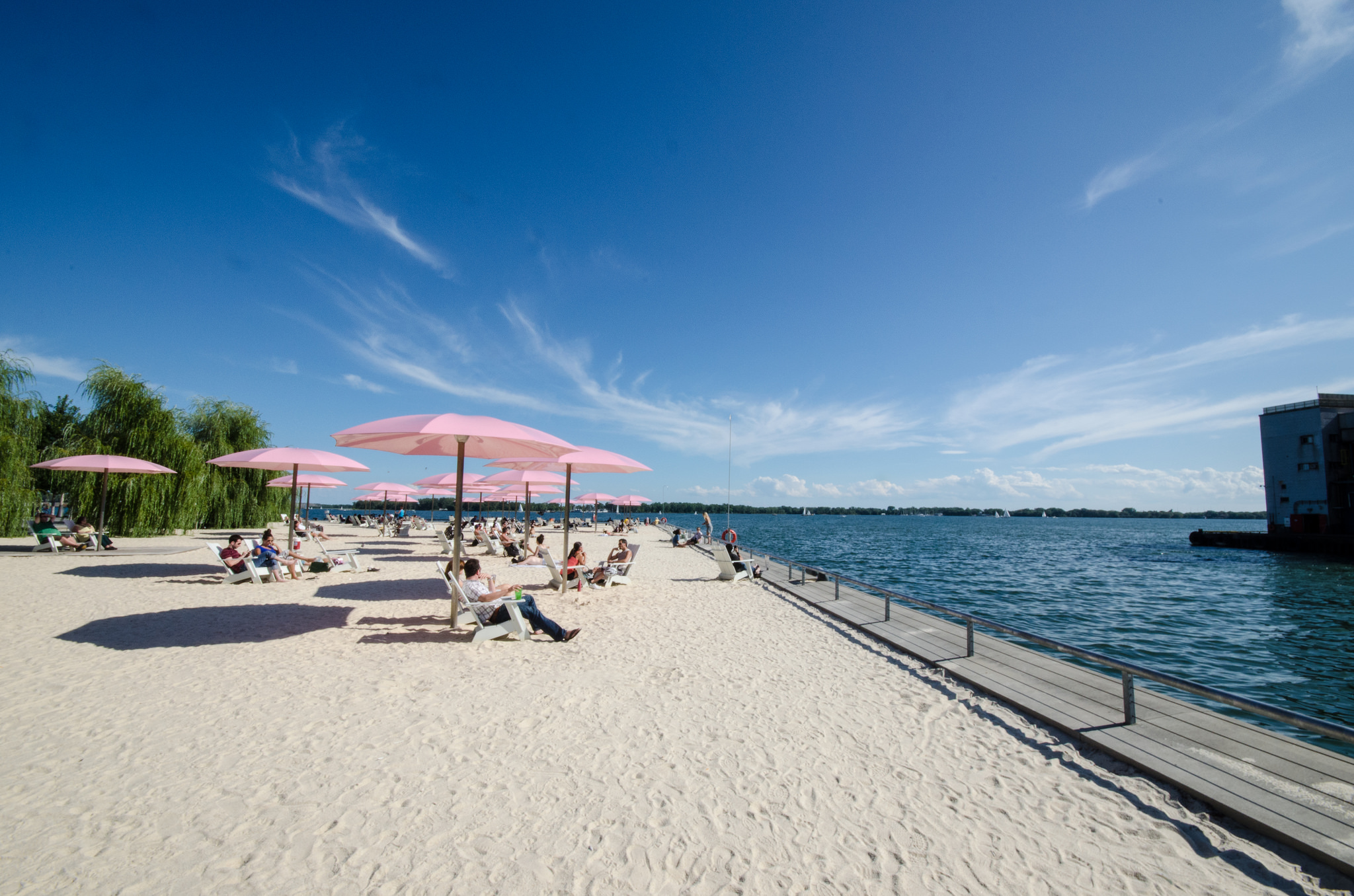 Photo of Sugar Beach in Toronto and Lakeshore. It's so bright and sunny and the water is a deep blue while the sky is a light blue.