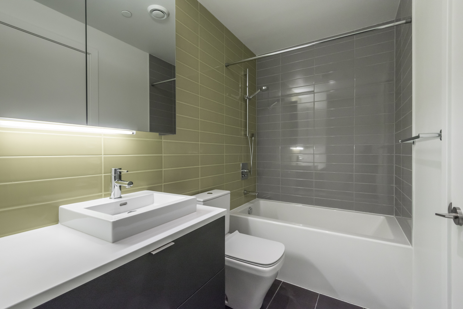 Image showing bathroom and tub. Also shows green and gray tiles, sink, and toilet.