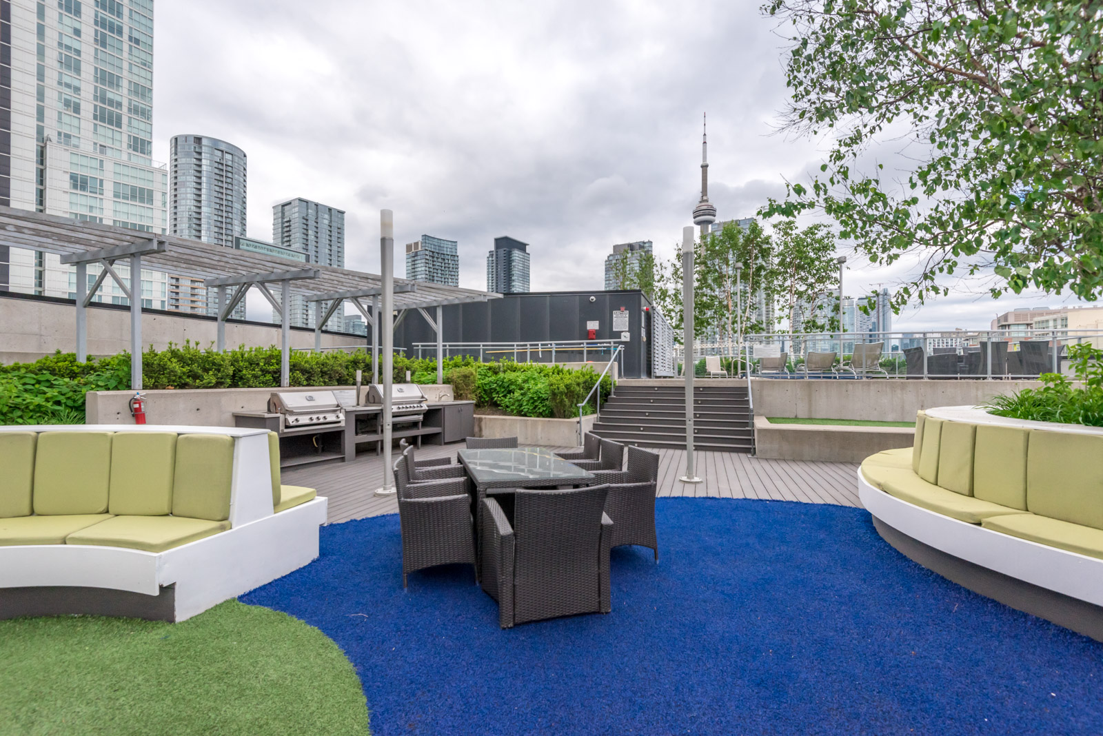 Outside view showing rooftop and chairs and CN Tower in the background.