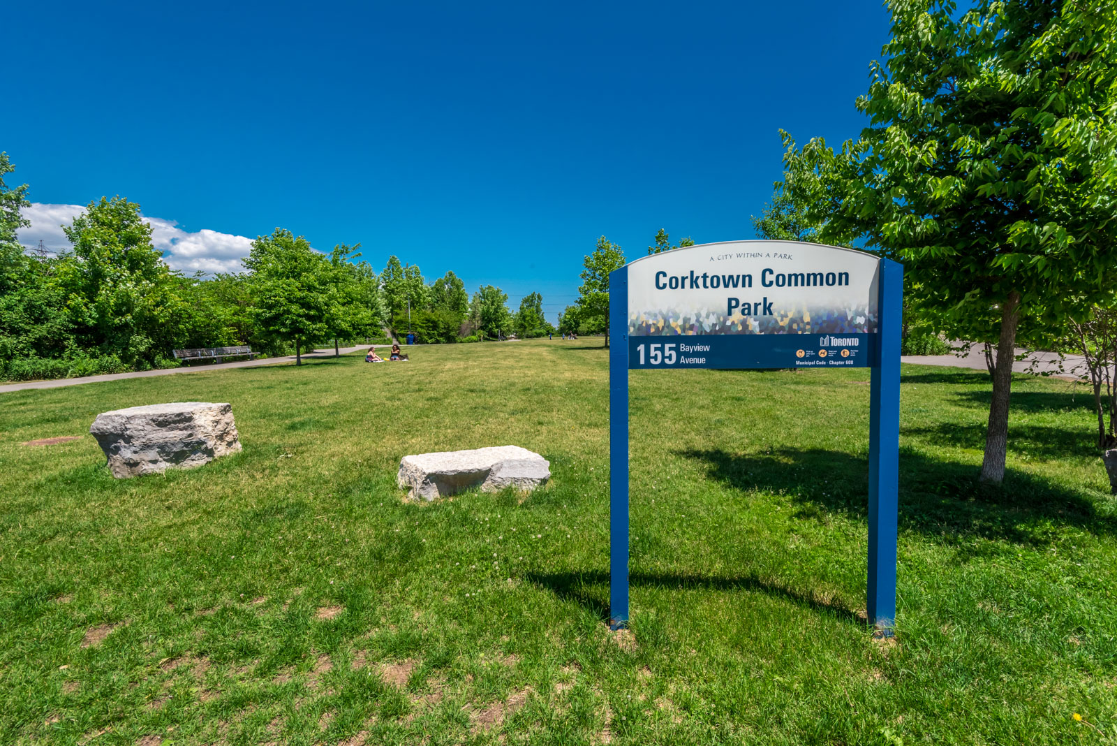 Picture showing Corktown Common Park and people. We see the park sign and also beautiful green grass.