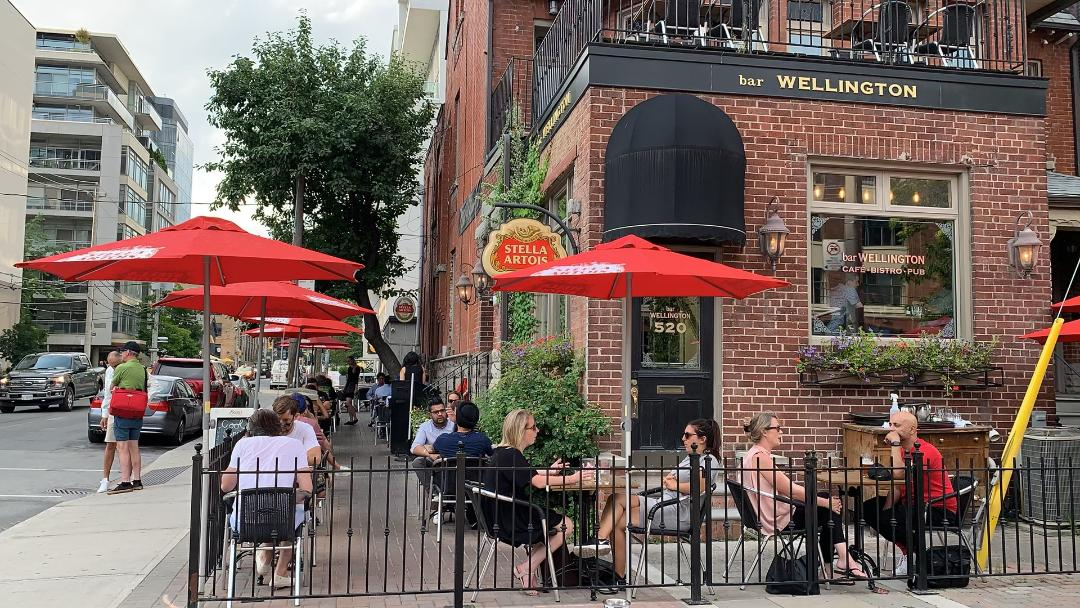 king west toronto wellington bar exterior patio orange umbrellas people