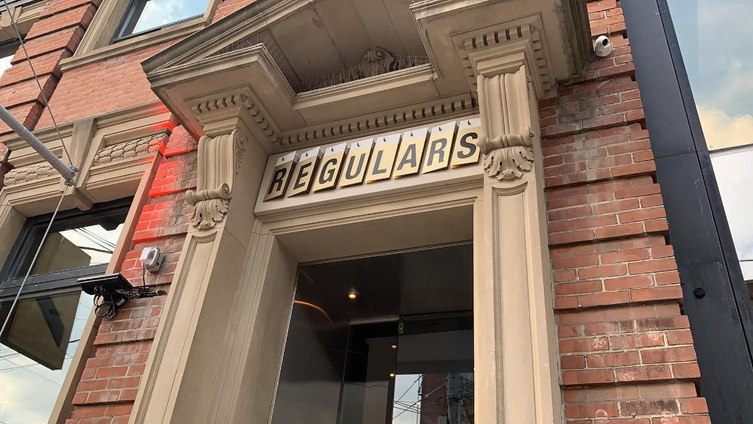 exterior of Regulars Bar with beige columns - King West Toronto.