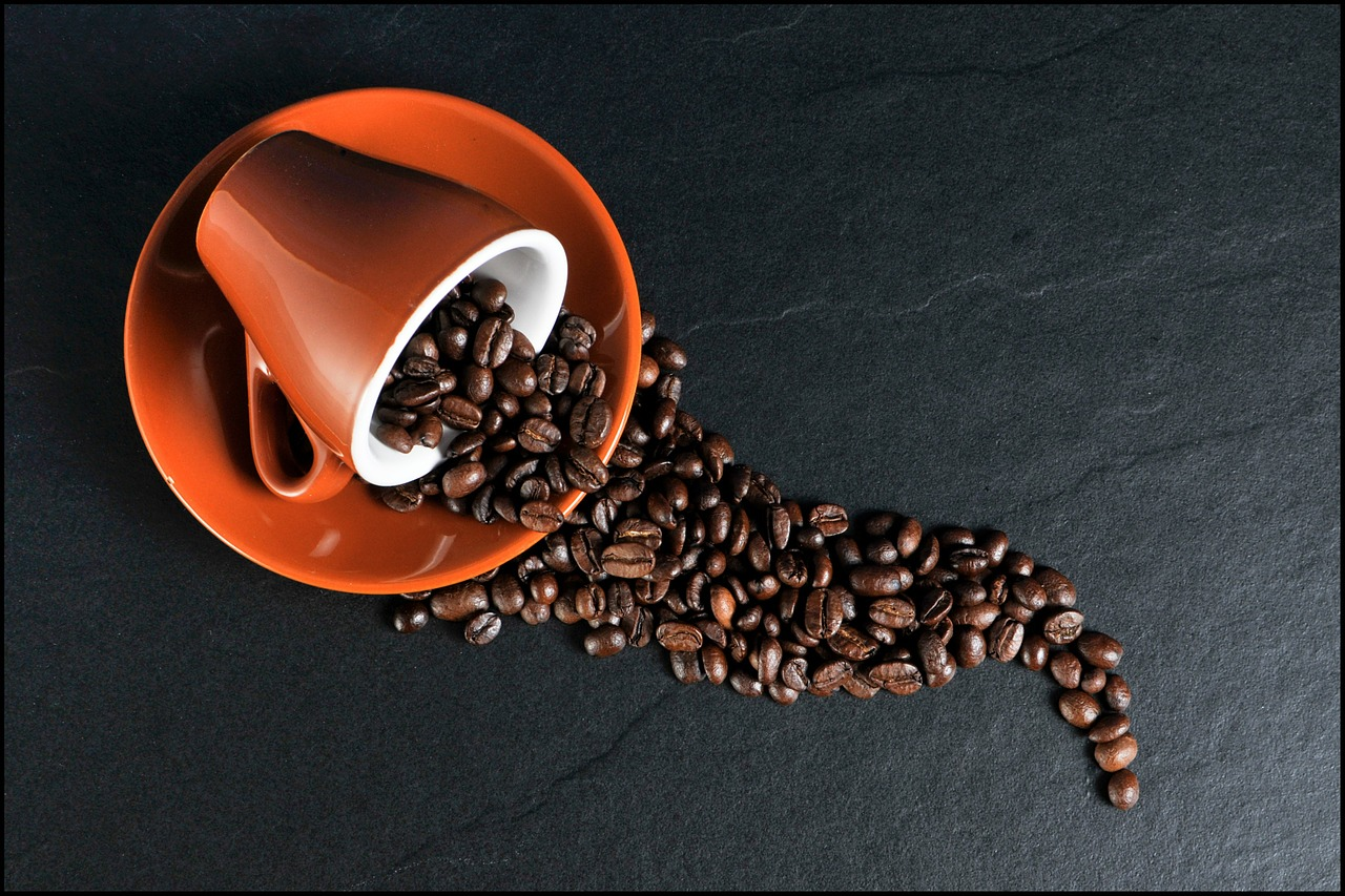 Orange coffee cup and saucer with spilled coffee beans on dark background.