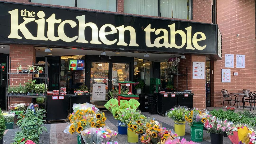 Exterior of The kitchen Table grocery store and flower pots outside King St W Toronto.