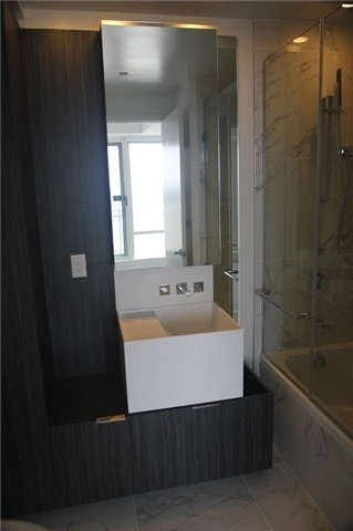 Image of 1 Bloor Unit 3809 master bath, with sink, cupboards and shower.