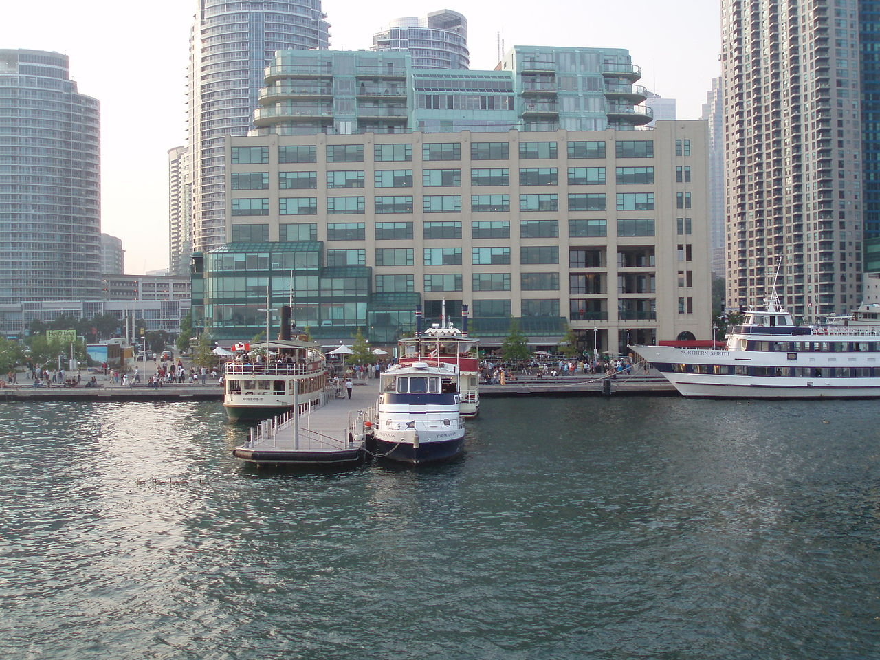 Another image of Toronto Harbour, this one showing ferries and people on the boardwalk.