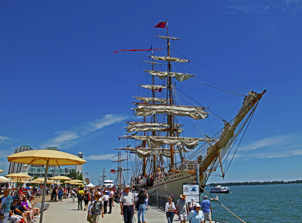 Tall-ship in Toronto Harbour and people walking along boardwalk.
