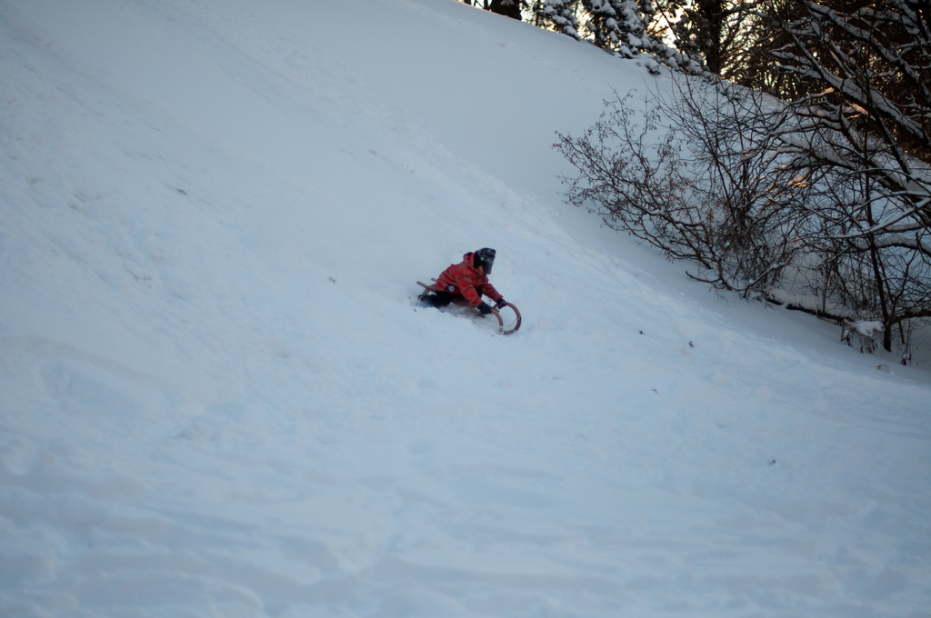 Kid tobogganing down a hill