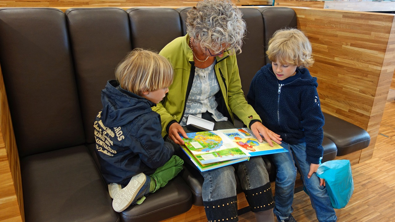 Kids and grandma reading book at library