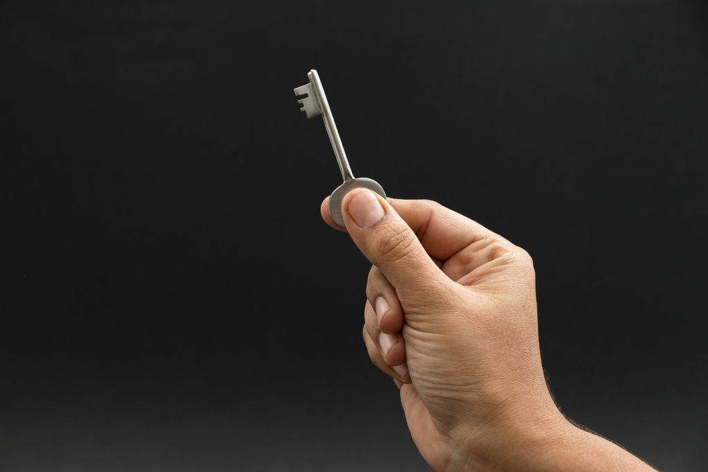 Hand holding key; shows how keeping interest rates steady can help people buy a home.