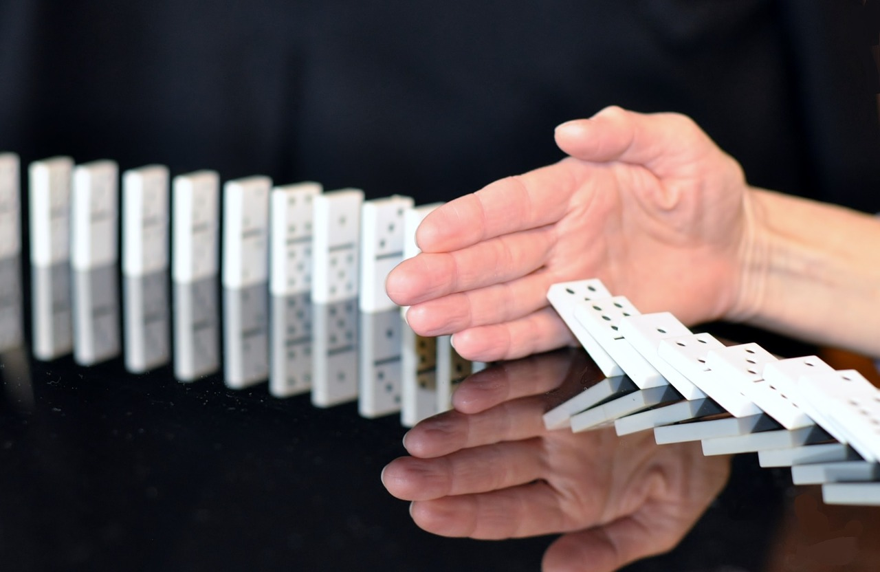 Hand stopping dominoes from falling over.