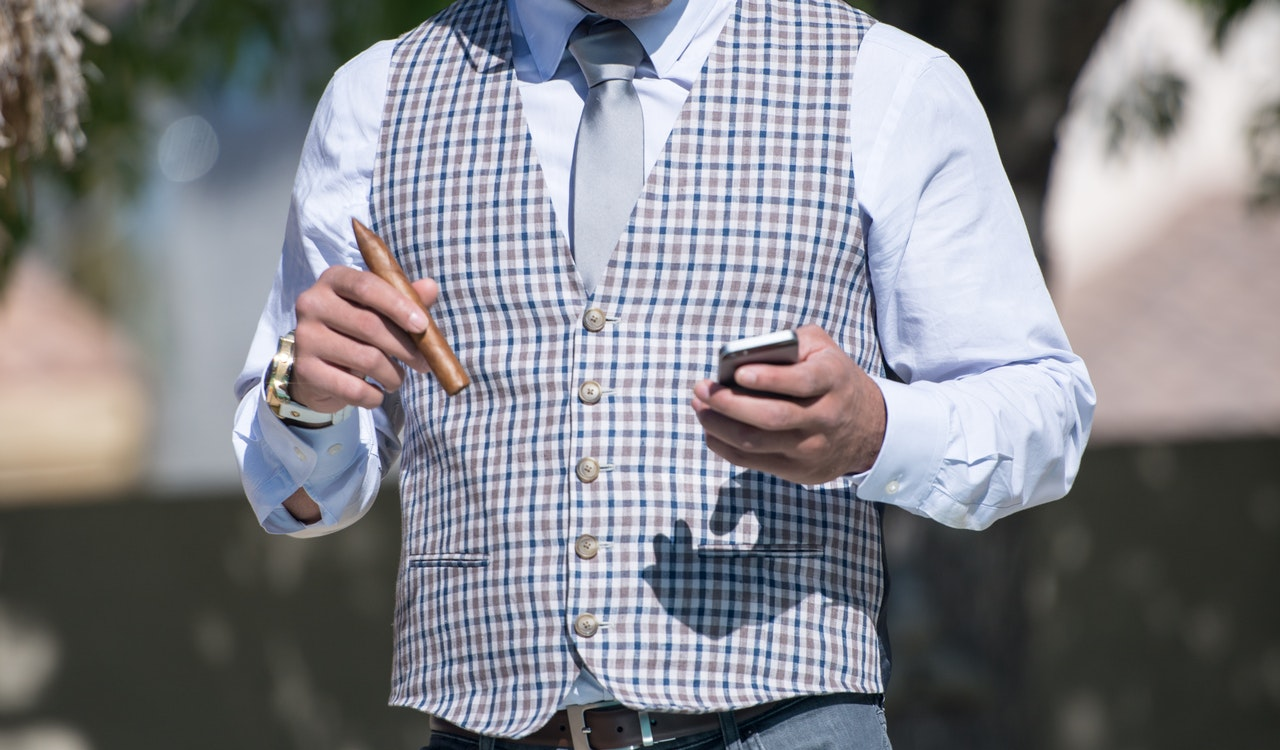 Image of man in fancy clothes holding cigar and phone. Shows how Rosedale is home to Canada's elite.