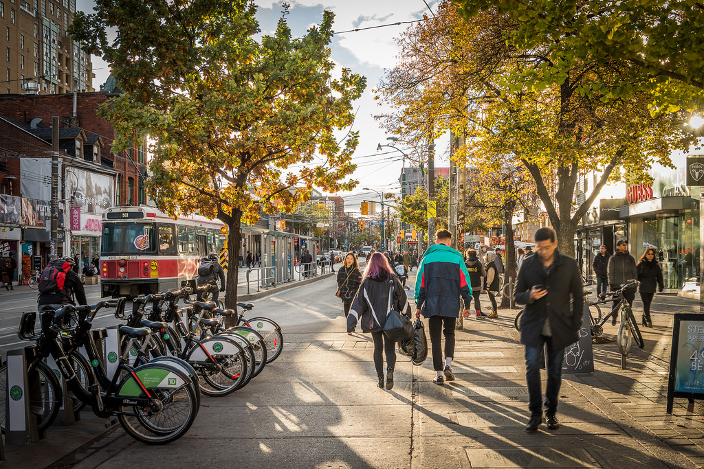 People, streetcars and bicycles along queen st w