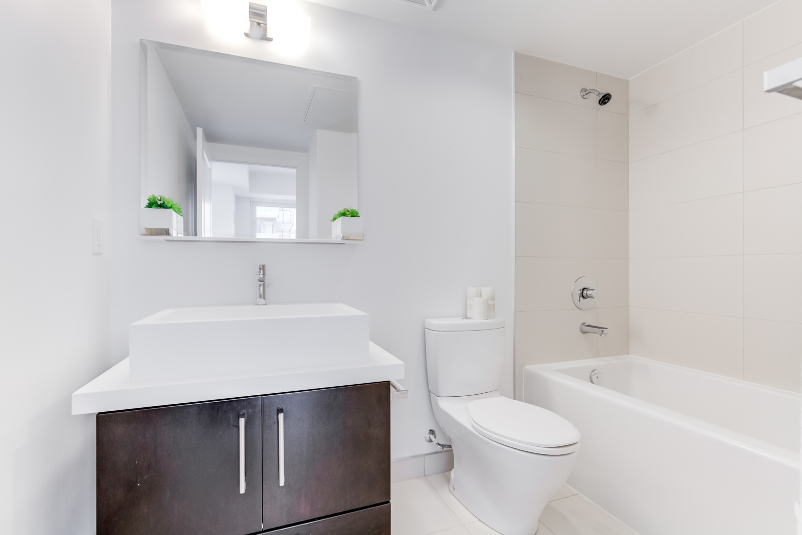 Master bath with white and gray colours and brown vanity.