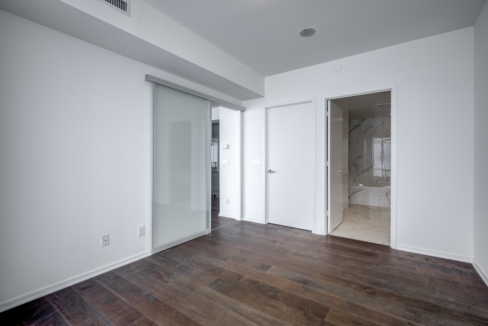 Sliding doors connect the master bedroom to the living and dining areas.