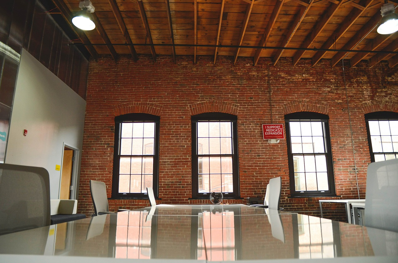 Meeting room with tables and chairs in warehouse office.