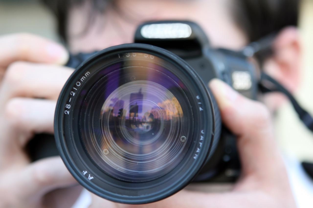 Professional photographer and Camera lens up close.