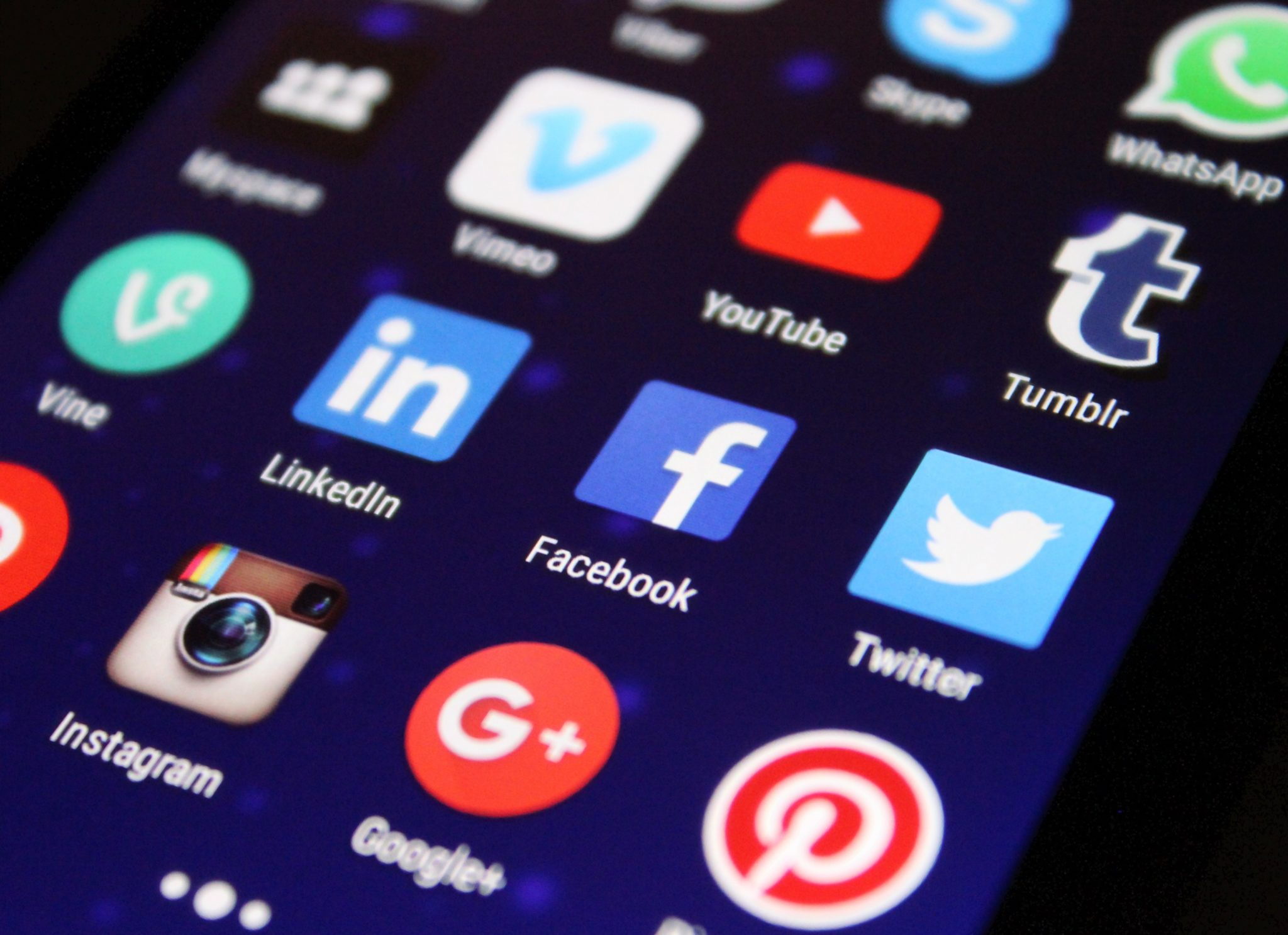 Close up of phone screen showing social media apps.