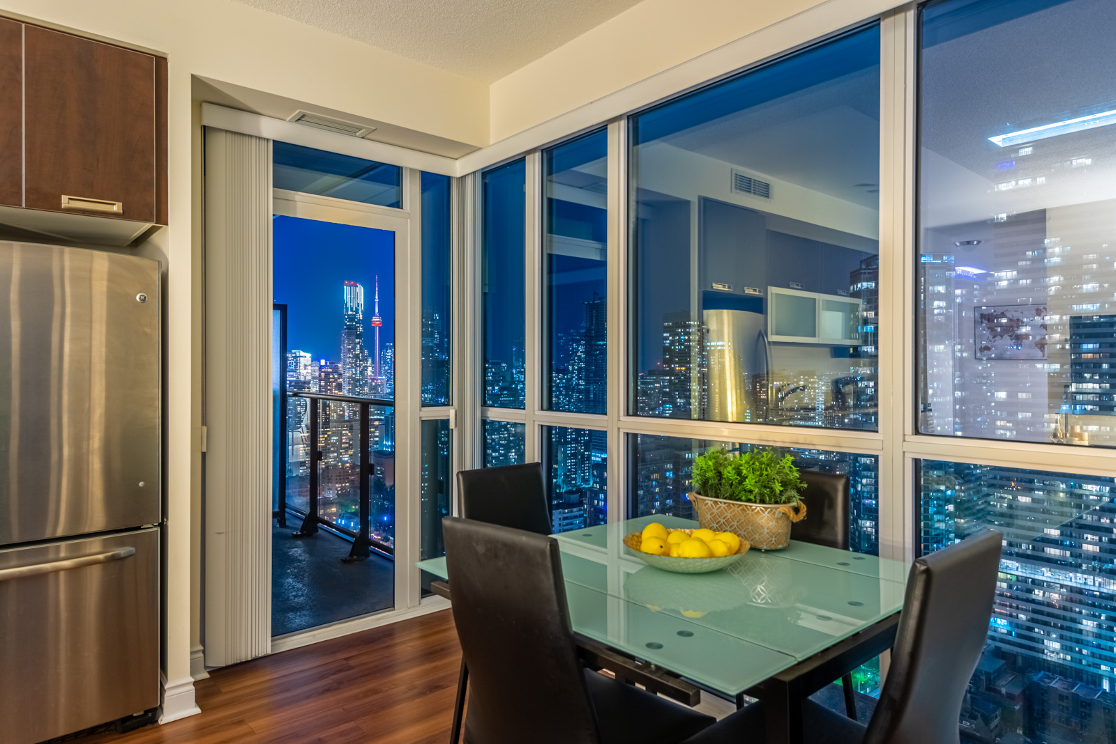 Dining room view of Toronto at night from 28 Ted Rogers Way Unit 3609.
