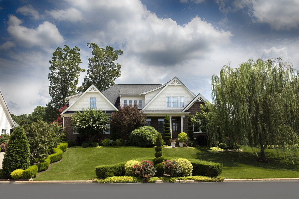 House and beautiful front yard showing importance of creating curb appeal pre-listing tip for sellers.