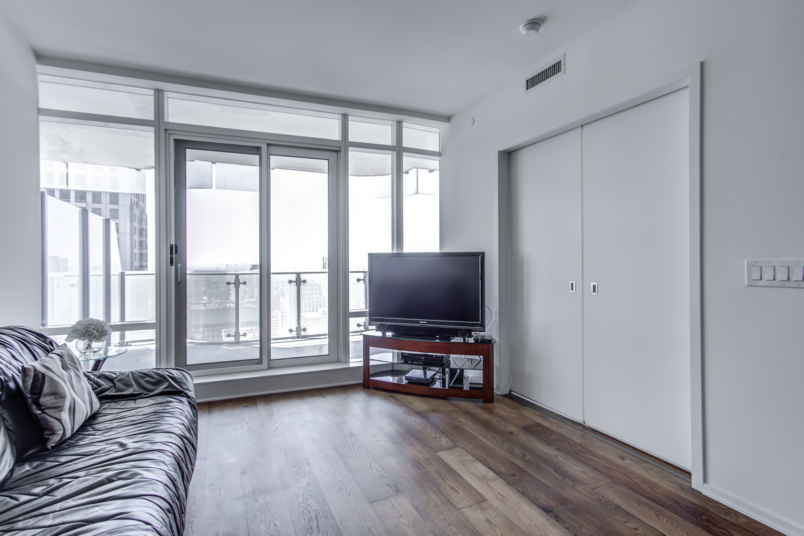 Photo of 1 Bloor St E Unit 3408 living room and balcony with huge windows.
