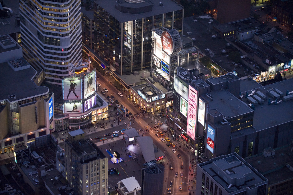 Aerial view of Yonge and Dundas in Toronto during night with electric billboards, buildings and pedestrians.