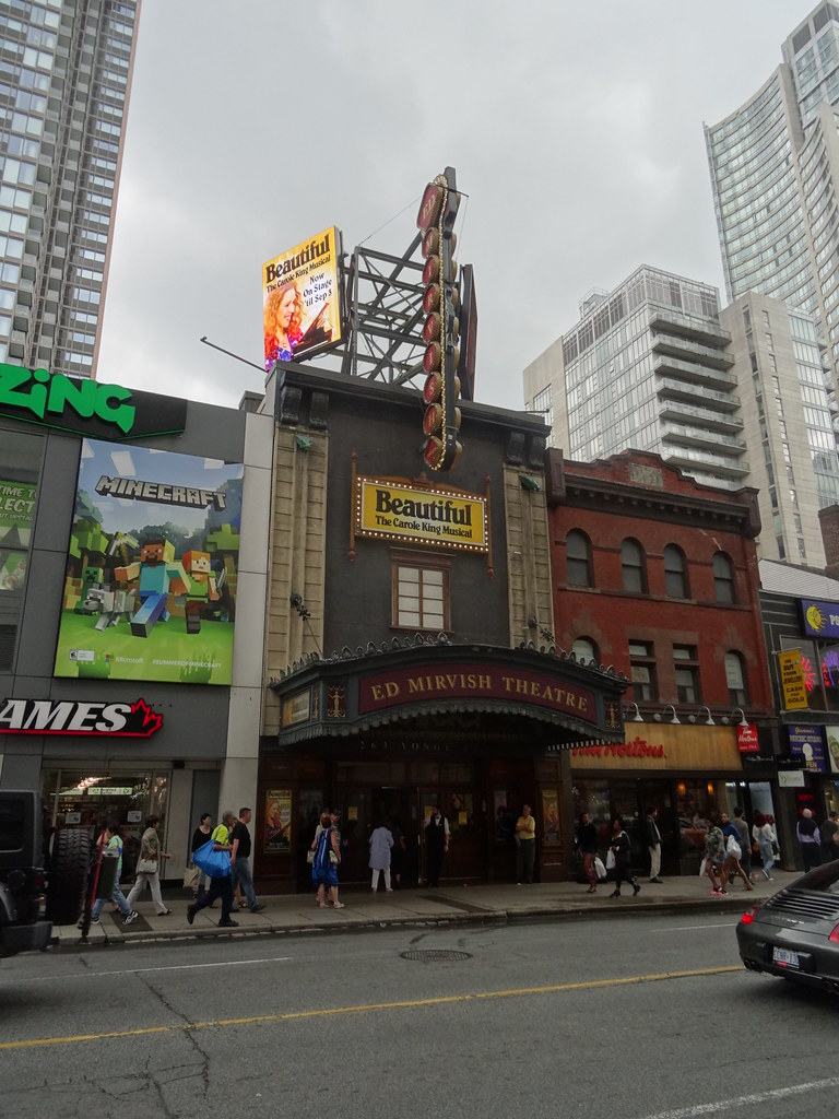 Exterior of Ed Mirvish Theatre on Victoria St in Toronto with pedestrians and billboards.