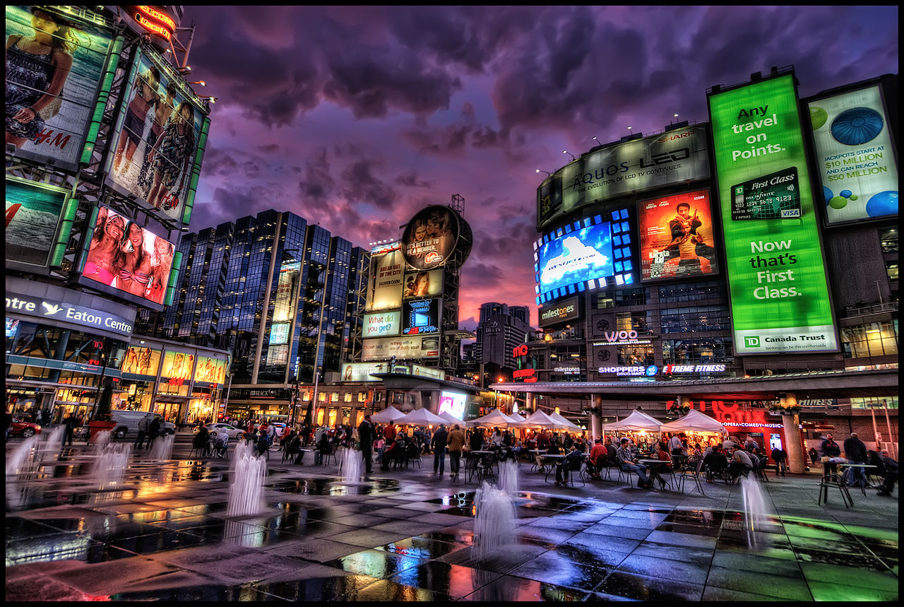 People and electric billboards at Yonge-Dundas Square in Toronto at night.