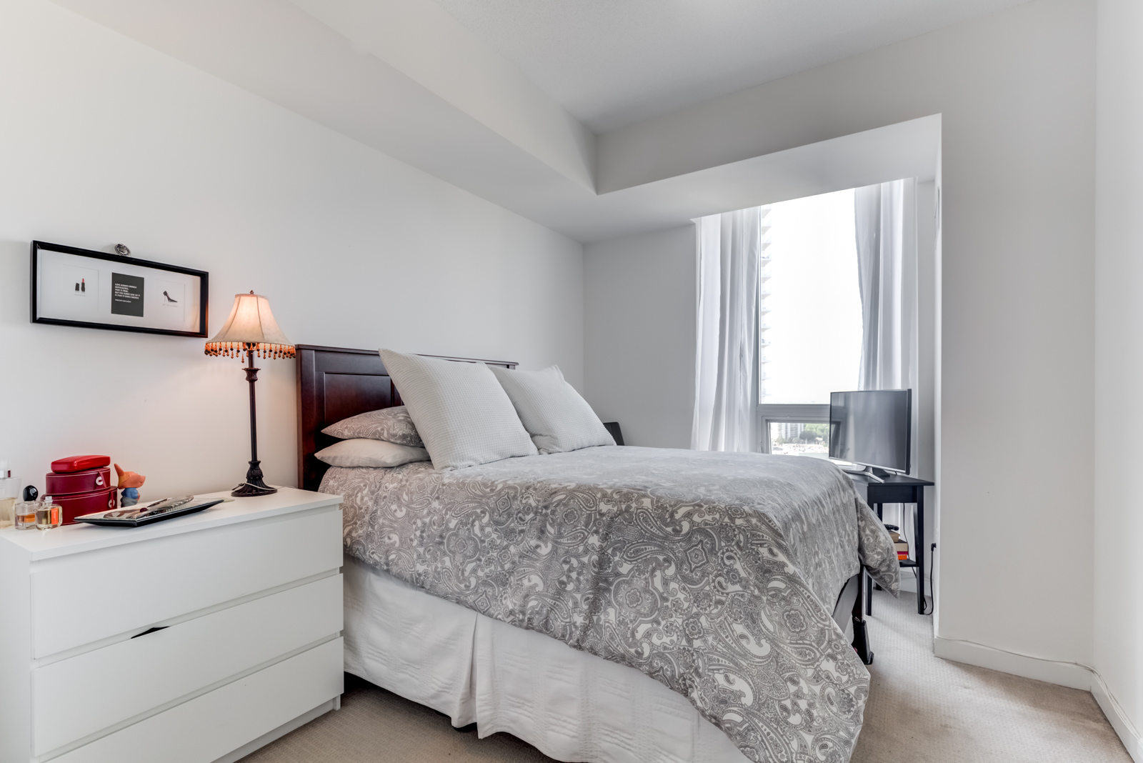Second bedroom at 62 Forest Manor Rd Unit 1803, Toronto with large bed, gray walls, bedside table and lamp.