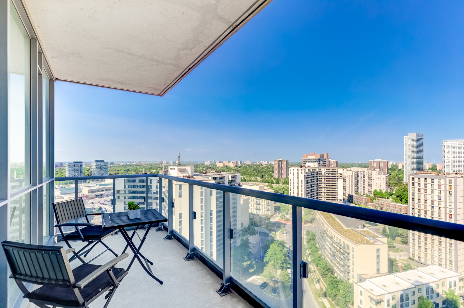 Glass paneled balcony with coffee table and chairs and view of North York, Toronto.