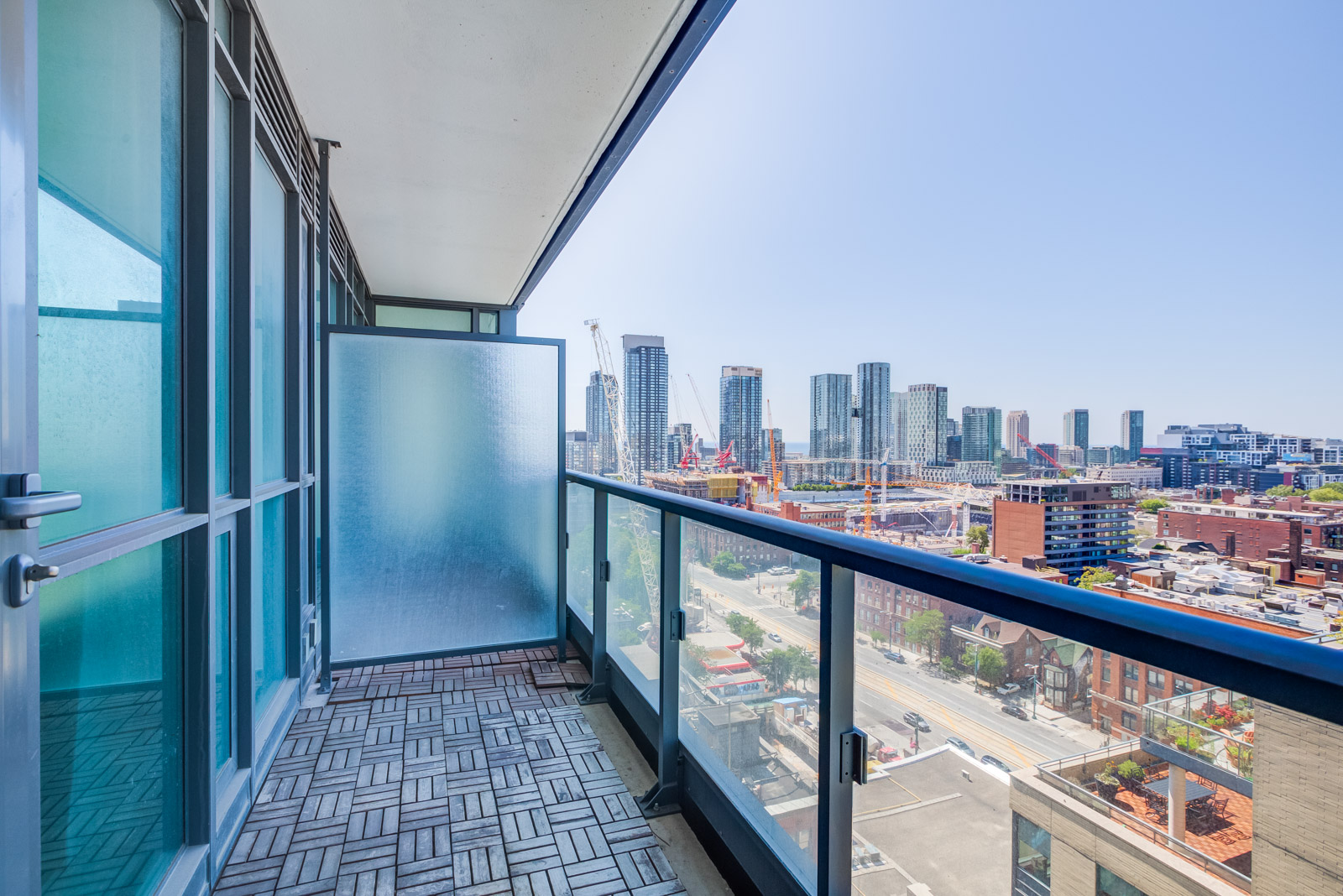 Balcony with glazed divider, glass panels and tiled floors overlooking King West in the Entertainment District.