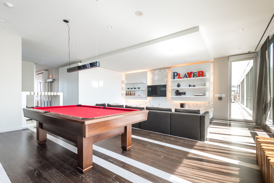 Billiards room and lounge with large, red-surfaced pool table, TV, and seating.
