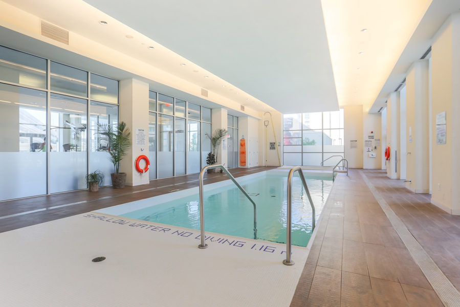 Indoor swimming pool with green water at Dream Tower at Emerald City Condos, Toronto.
