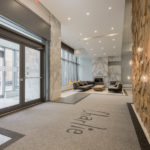 Charlie Condos lobby with high ceilings, pot lights, carpeted floors and light bulbs hanging from a rock-wall.
