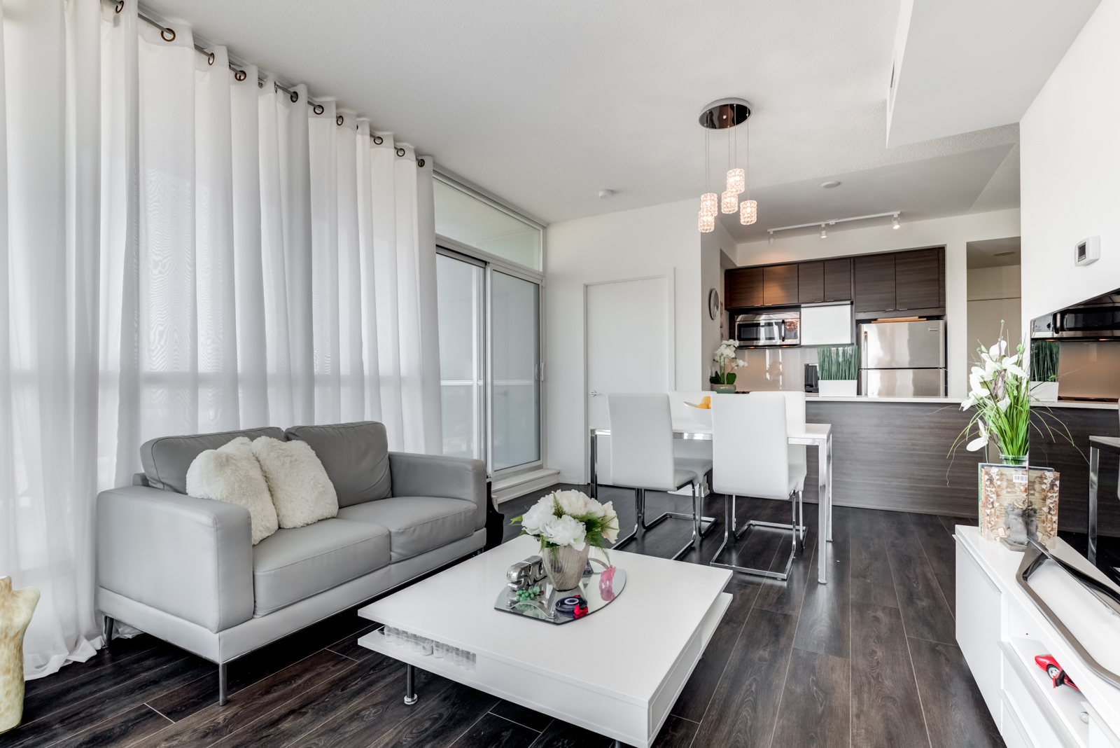White and gray curtains, walls, furniture and dark floors at 62 Forest Manor Rd Unit 1803, Toronto.