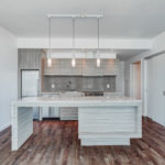 Kitchen breakfast bar with marble top and wooden base along with cabinets and appliances.